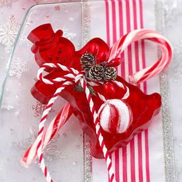 Candy Place Setting:   Jazz up a place setting by using a translucent red cookie cutter as a party favor. Tuck a candy cane through the cutter's handle, then tie it up with red-and-white cord and a sprig of tiny pinecones and berries.