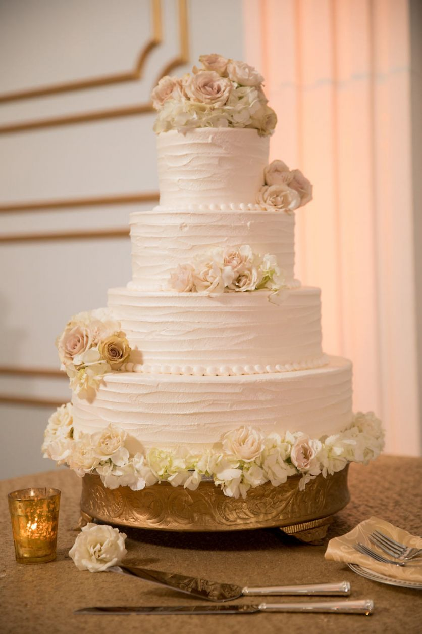 Four Tier Round White Wedding Cake With Blush And Ivory Roses On Gold Stand