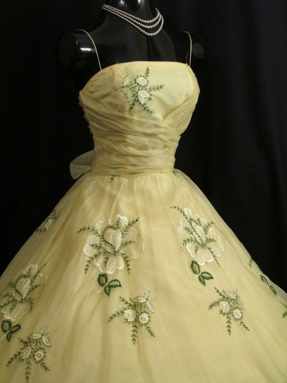 An adorable original 1950's party/prom dress in a stunning lemon silk organza decorated with exquisite floral embroidery. The style typifies the 50's - oh so feminine and figure flattering – narrow bodice with a twirling full skirt.