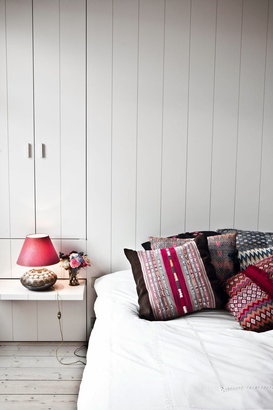 richly coloured cushions in monochrome bedroom in