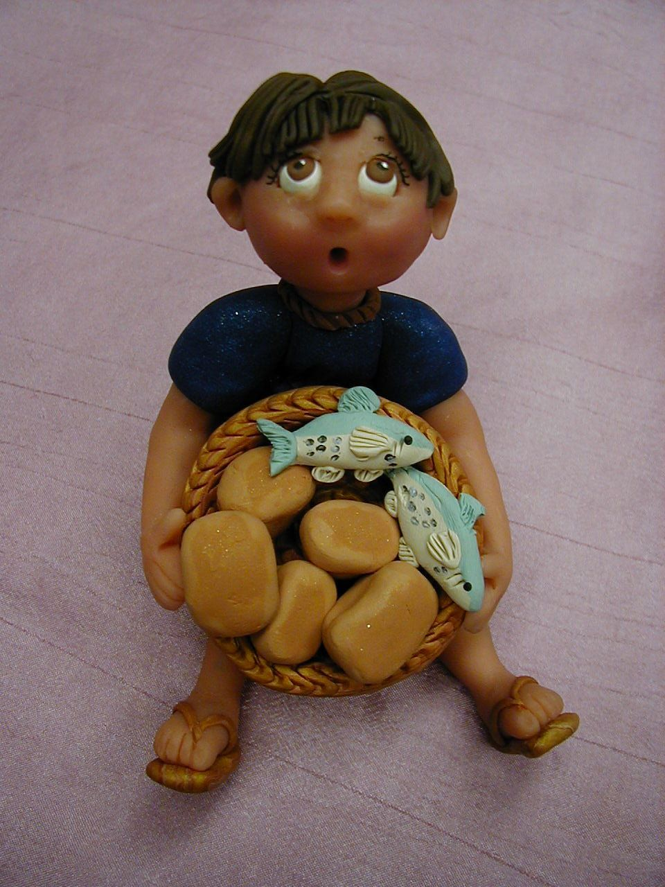 Boy with the two fish and five loaves of bread which for Loaves and fish