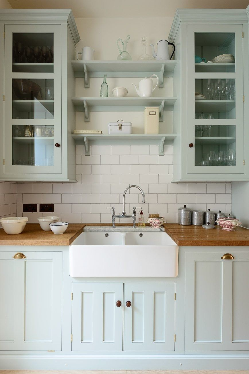 Palest blue kitchen cabinets topped with an apron sink and butcher