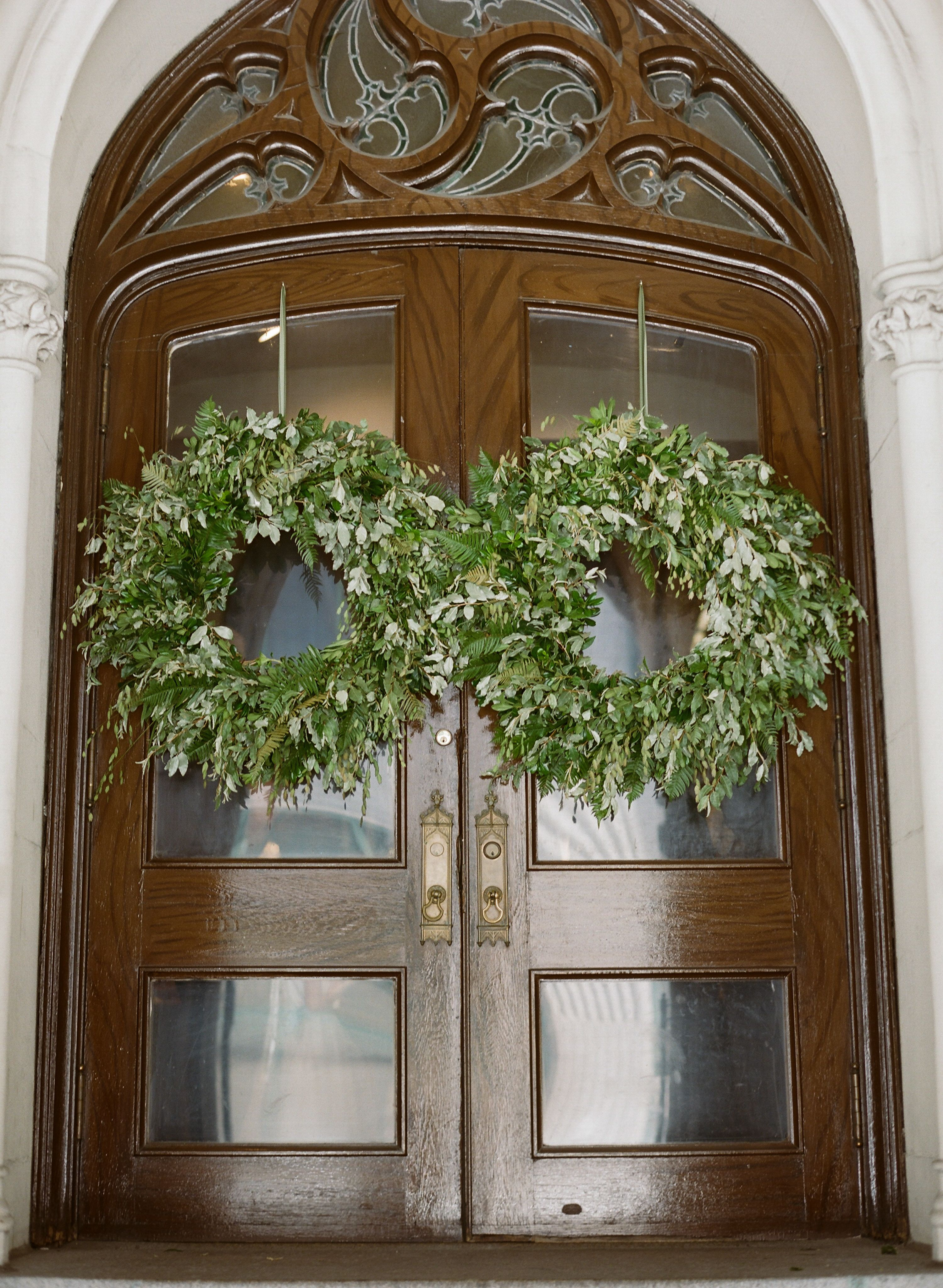 Seasonal fresh wreaths hanging on the church doors for a wedding ...