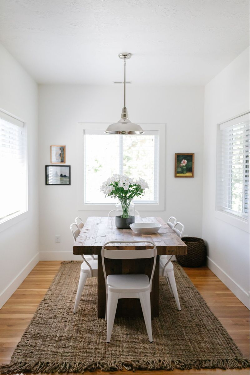 Create a cozy modern farmhouse dining space with West Elm reclaimed wood table, affordable jute rug, vintage inspired art, oversized basket for storage, bowl and vase filled with fresh flowers. #diningnook #kitchennook #diningroomtable