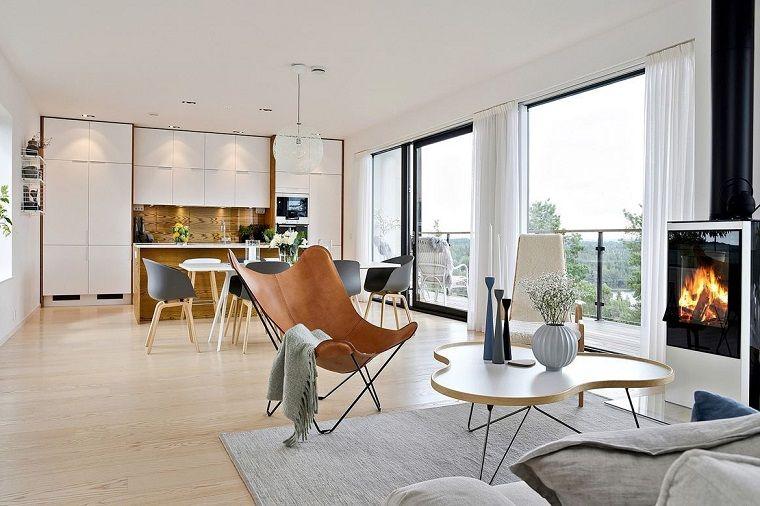 Soggiorno con divano e poltrona di legno, camino moderno, cucina ...