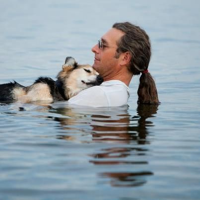 """""""This 19 year old Shep being cradled in his father's arms last night in Lake Superior. Shep falls asleep every night when he is carried into the lake. The buoyancy of the water soothes his arthritic bones. Lake Superior is very warm right now, so the temp of the water is perfect. I was so happy I got to capture this moment for John. By the way, John rescued Shep as an 8 month old puppy, and he's been by his side through many adventures"""".    Photo: Copyright Stonehouse Photography"""