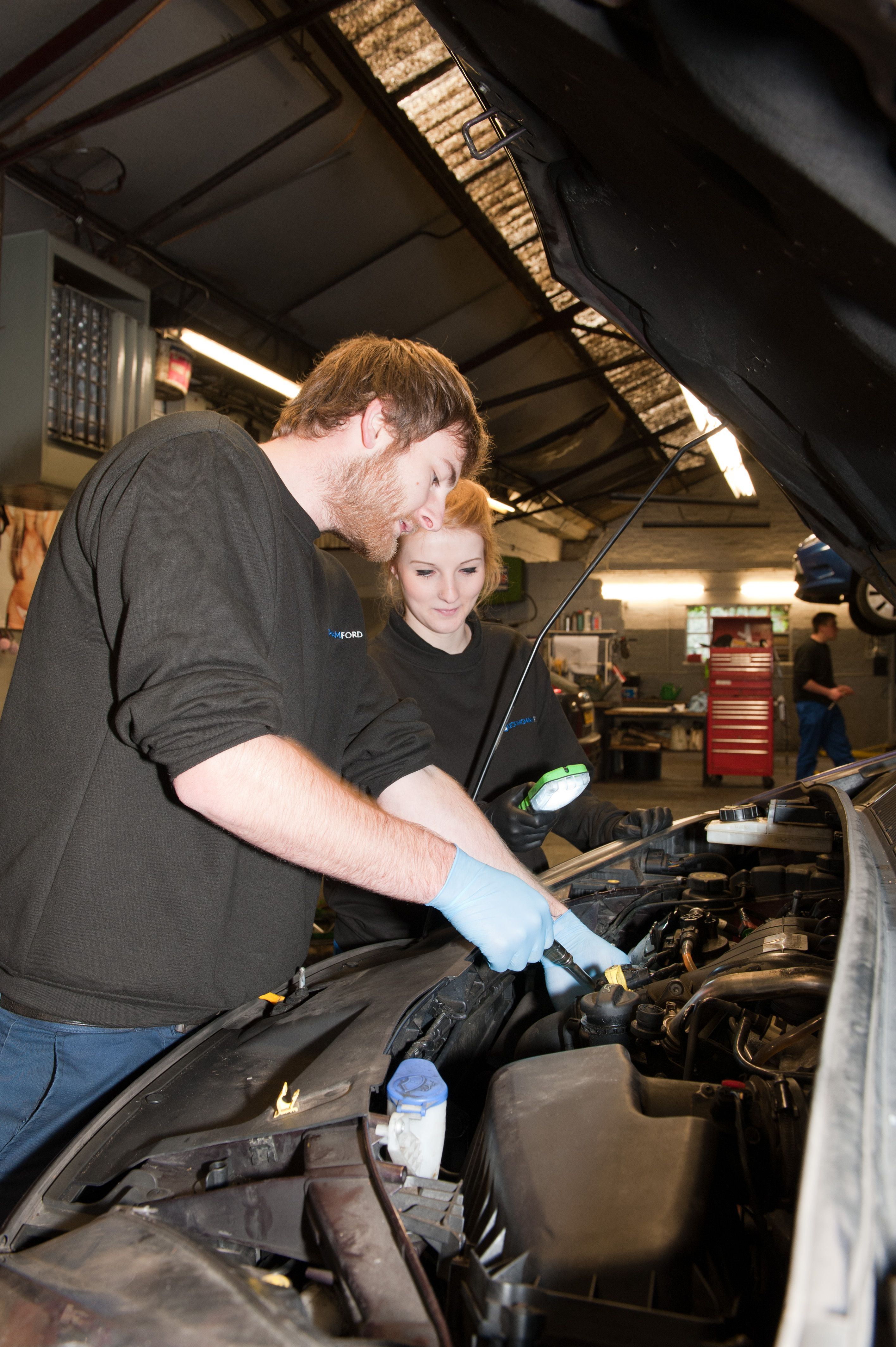 Scott and Chloe working on a car. carservice buckingham
