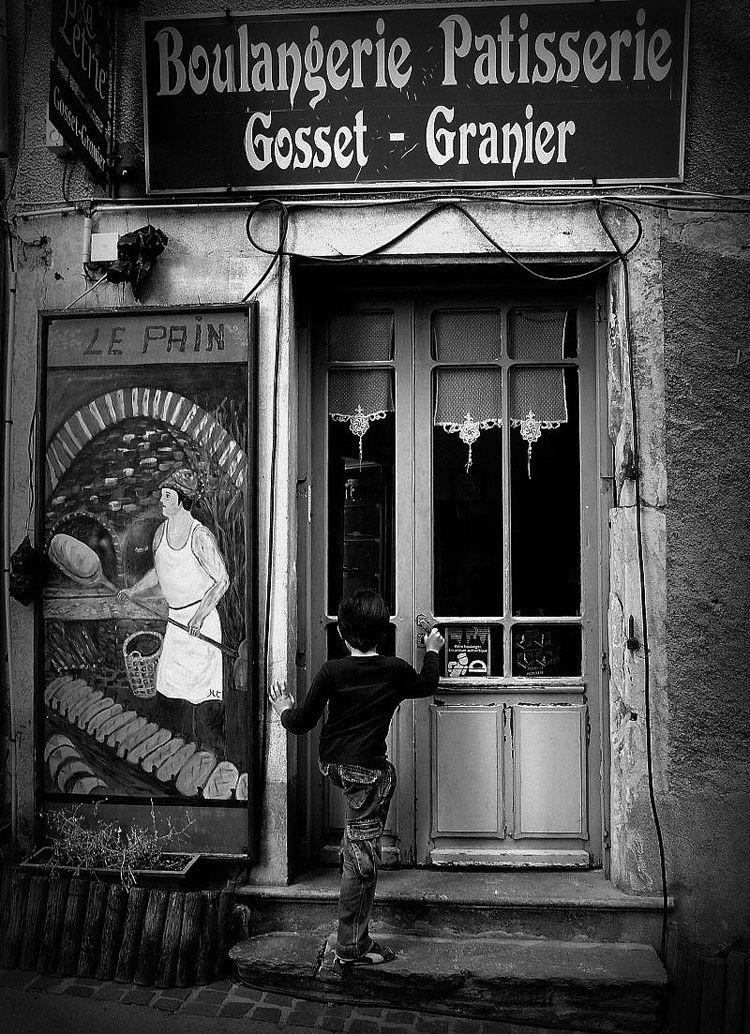 Enfant qui ouvre la porte du boulanger © Willy RONIS