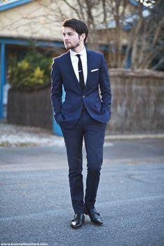 Handsome groomsmen in a simple navy suit and skinny black tie ...