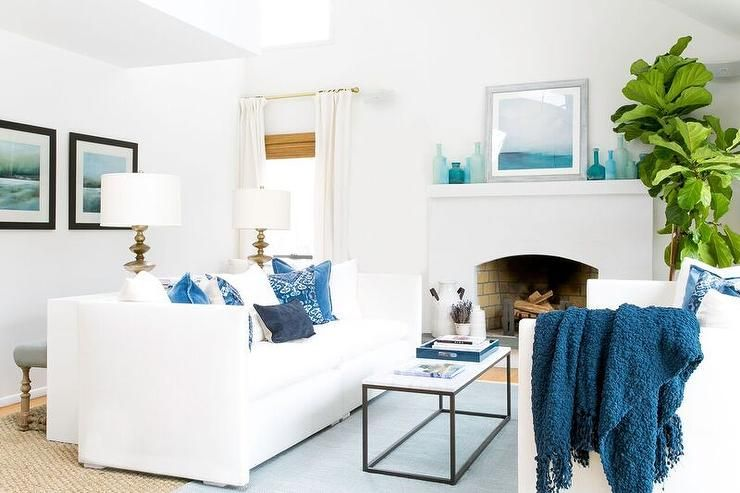 White And Blue Coastal Living Room Features White Shelter Back Sofas Draped In Blue Pillows And Affordable Interior Design Interior Design Coastal Living Rooms