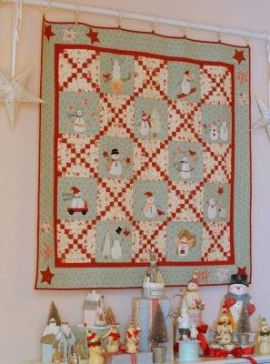 Cute snowmen quilt displayed behind a snowman collection in a dining room / Bunny Hill Website