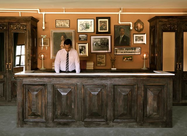 old west hotel front desk elements like vintage books stacked in the cabinets glass bottles wall dcor