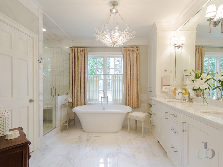 Transitional bathroom features a crystal chandelier over a for Master bathroom curtains