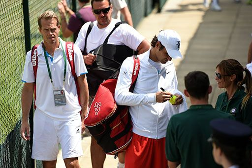 Roger Federer stops to sign an autograph next to his coach Stefan Edberg