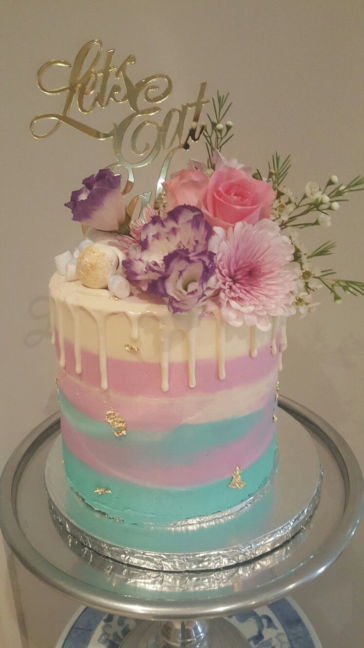 A Drip cake with fresh flowers meringues and mini marshmallows I