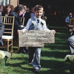 """This couple got creative with their ceremony sending their nephew down the aisle with a """"Here Comes Your Girl"""" sign. Photo by Brandon Scott."""