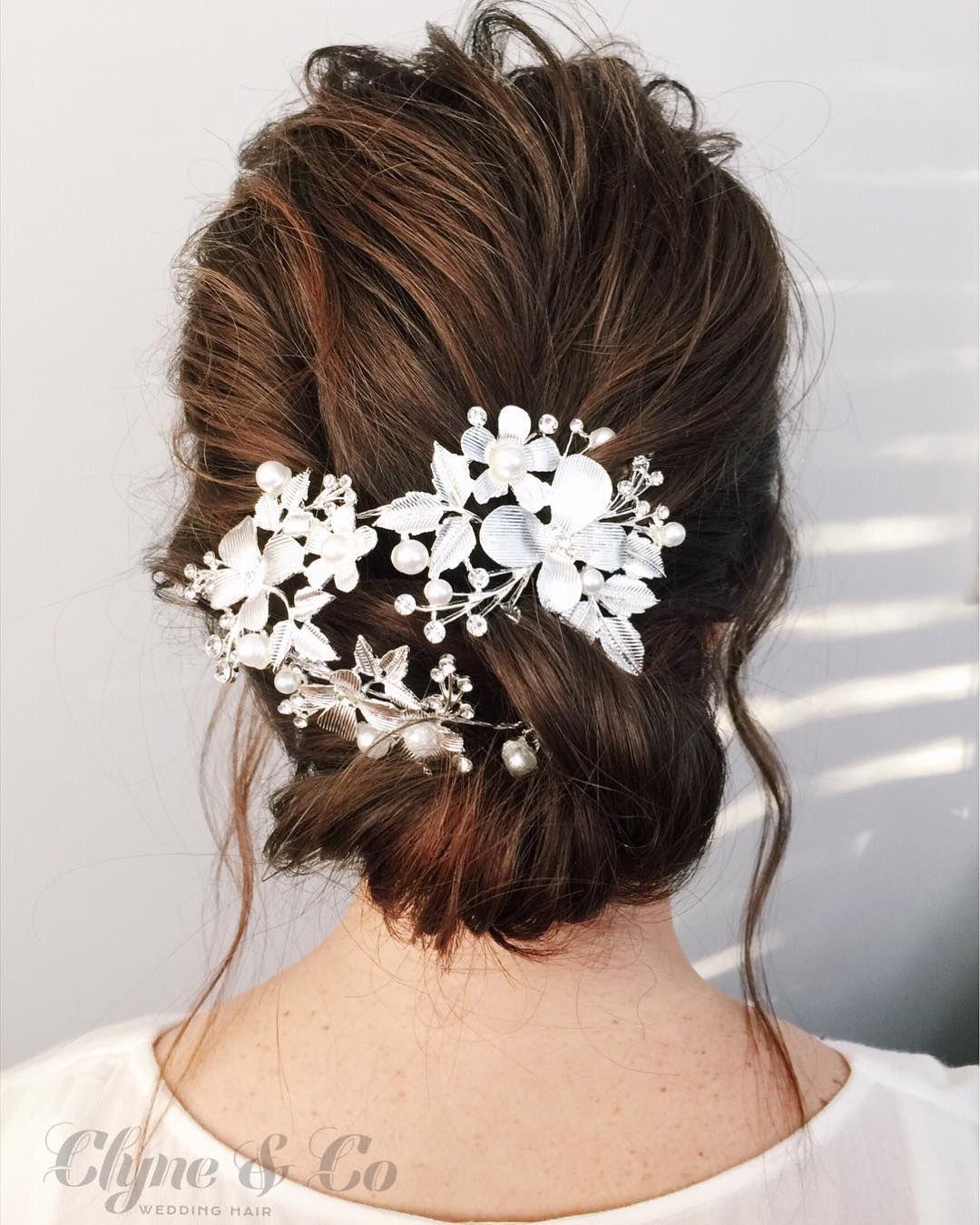 Μοντέρνα νυφικά χτενίσματα  Κότσος χαμηλός με λεπτομέρειες από λευκα  λουλούδια αξεσουάρ. 6d4bd8d1108