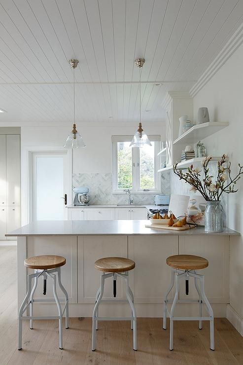 U Shaped Kitchen Features White Shaker Cabinets Paired With Light Gray  Quartz Countertops, Caesarstone Clamshell