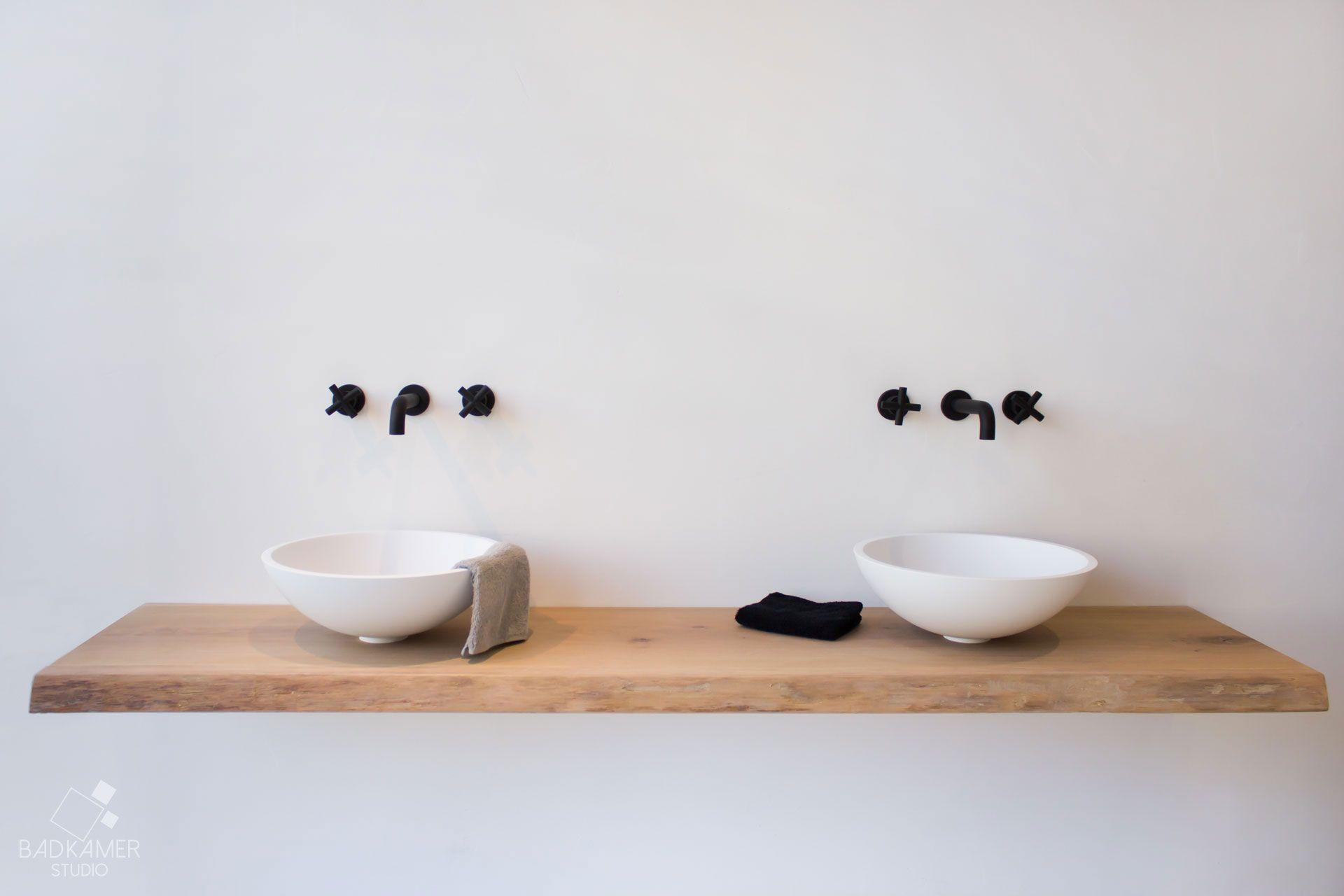 Maatwerk badkamer met een organische look. Voor de muur van deze badkamer is gebruik gemaakt van Kerlite tegels die niet van echt hout te onderscheiden zijn. Daarnaast is de badkamer voorzien van Solid Surface waskommen en ligbad met opbergruimte voor uw handdoeken of mooiste boeken. Verder zorgen de mat zwarte inbouwkranen voor een mooi contrast. De matzwarte uitloop welke vanuit het plafond water in het bad laat lopen is toch wel het middelpunt van deze badkamer #badkamerstudio