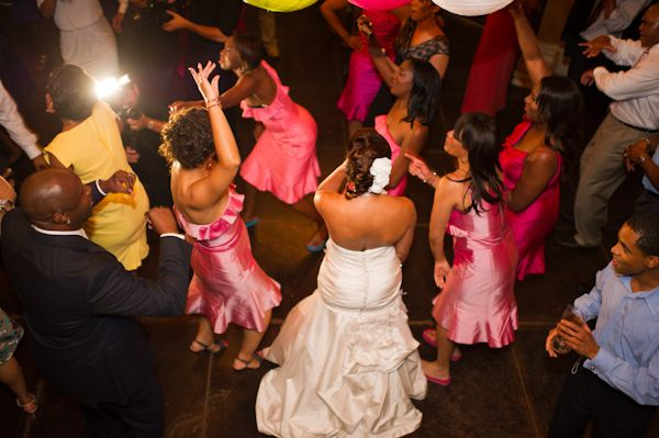 Bridesmaids in hot pink help a bride get down on her wedding day.