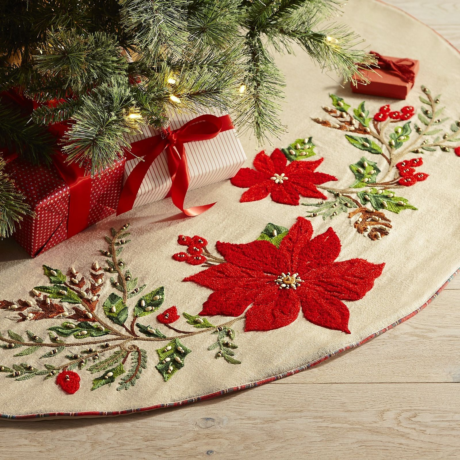 Pretty poinsettias on a soft, natural backdrop make our tree skirt an elegant addition to any holiday decor. The classic embroidered motif makes a perfect foundation for beautifully wrapped presents and a perfectly decorated tree.