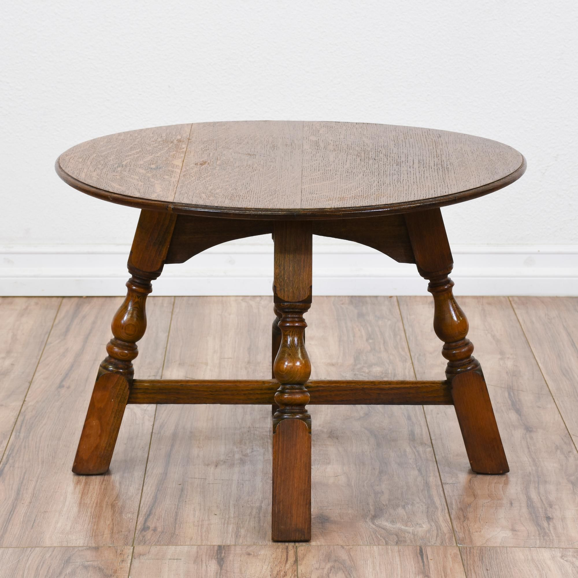 This rustic round end table is featured in a solid wood with a raw