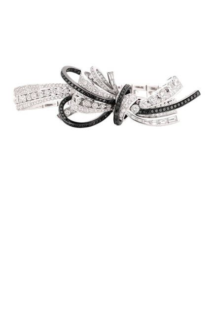 The 1932 Collection..The Ruban Couture bracelet in 18K white gold set with 382 round-cut diamonds, 10 baguette-cut diamonds, and 94 brilliant-cut black diamonds.