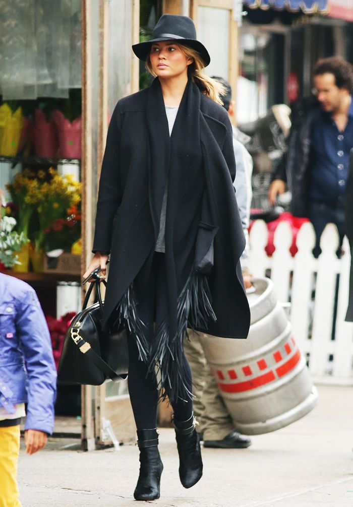 Chrissy Teigen wears a gray t-shirt, coat, fringe scarf, skinny jeans, boots, and a fedora