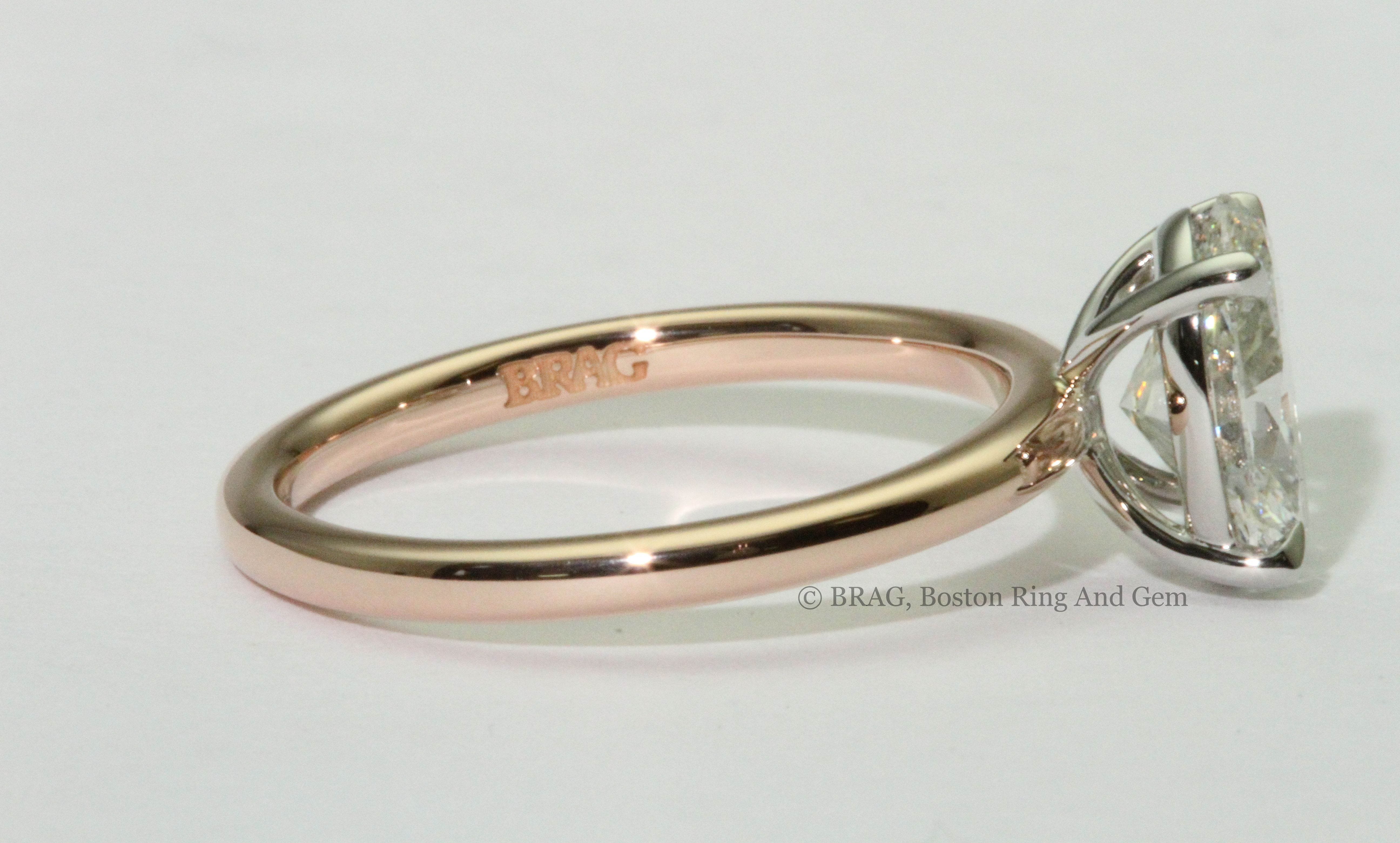 oval cut center diamond set in platinum basket head and rose gold