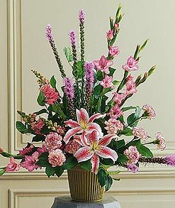 "Triumphant Triangle   This beautiful arrangement with its purple and pink flowers reminds us that love carries on. One arrangement with lavender gladioli, purple liatris, pink snapdragons and lilies, and soft cascading foliage arrives in a simple green container. Approximately 31"" W x 33"" H - Orientation: One-Sided http://www.pjsflowers.com/triumphant-triangle/"