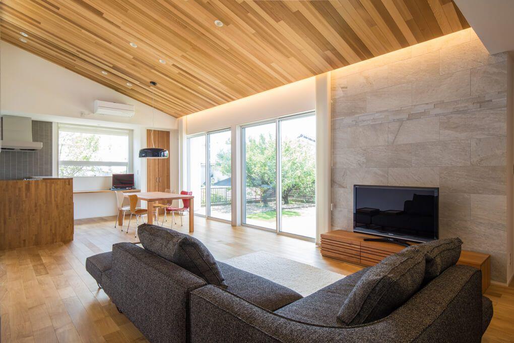 天井の無垢材とダイナミックな天然石の壁 間接照明がldk全体を