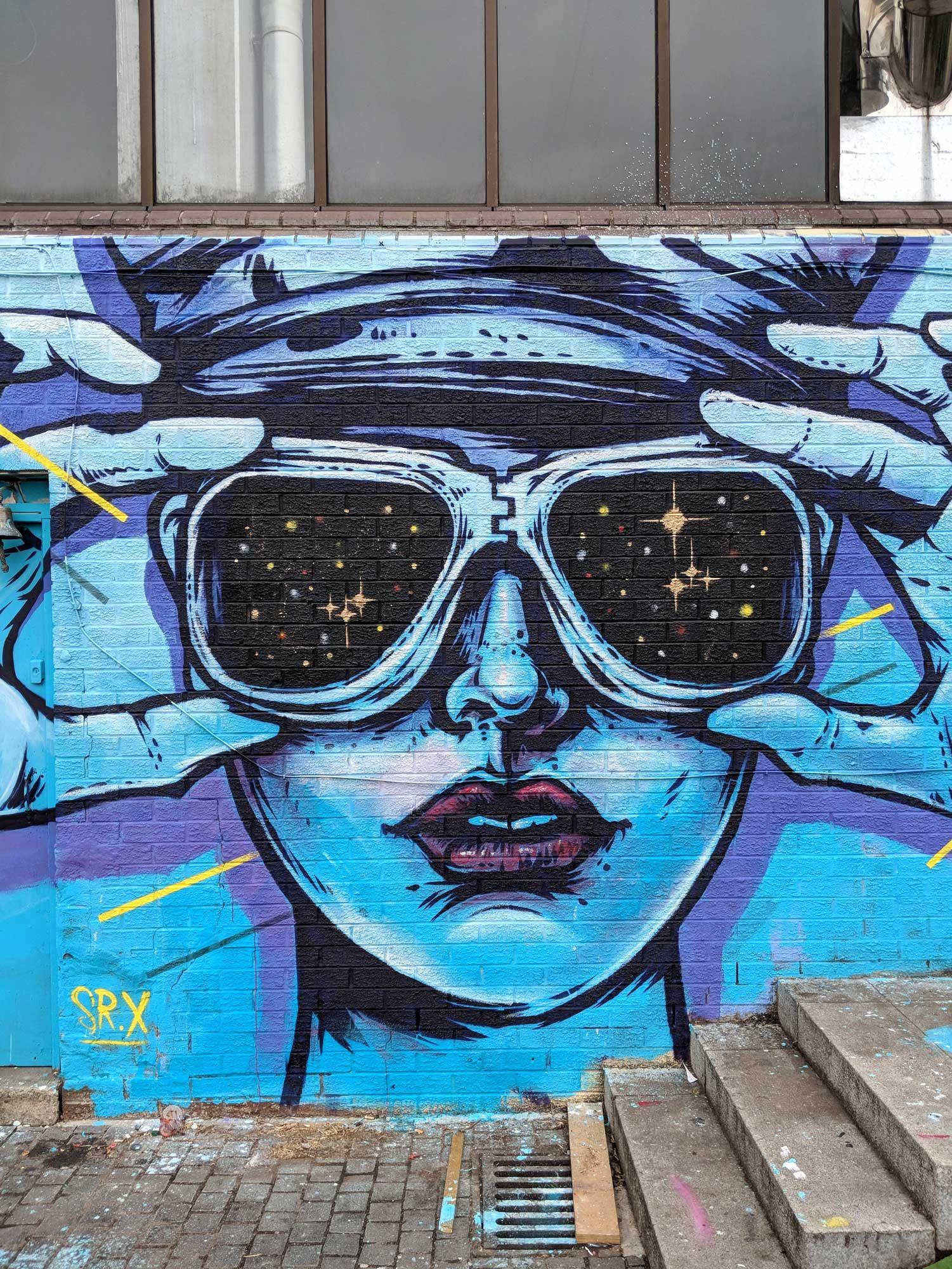 Enlightenment. By Sr. X. Street art mural painted in Manor House, London. . . . . . pop art, surrealism, illustration, grafitti, mural , stencil, paint, pintura, arte urbano, urban, ink, blue, fire, lighter, retro, vintage, ad, advert, americana, 50s, 60s, woman, space, stars, vision, glasses #graffitiart