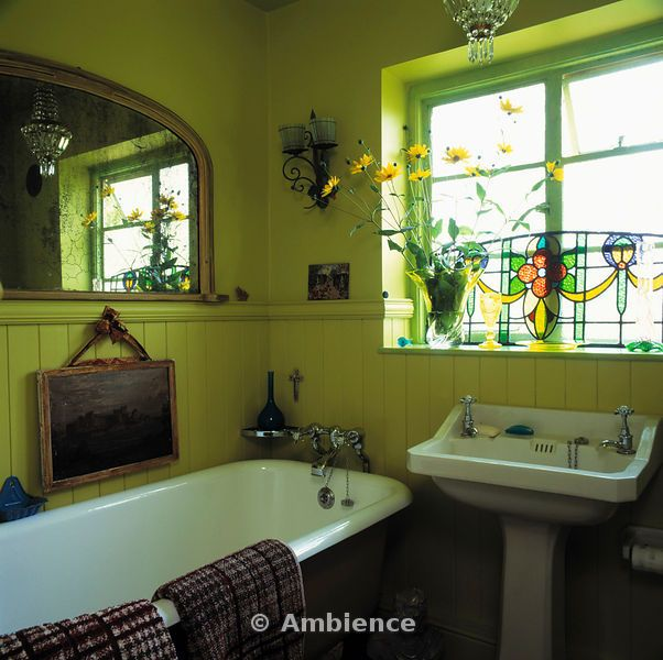 Stained glass panel on window above basin in lime green bathroom