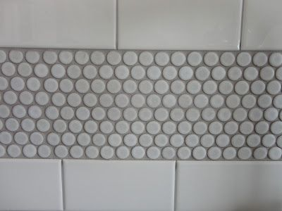 white subway tile, gray grout broken up with penny tiles.