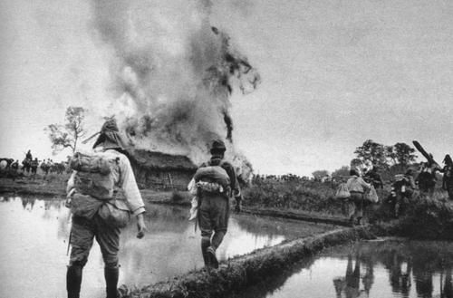 japanese soldiers pasing by a house burned by defeated chinese (china, november 1944)