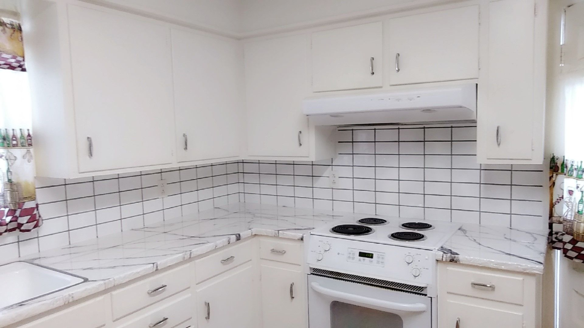 Black and white marble countertops with unfinished rock edges and white subway tile with gray grout for the back splash