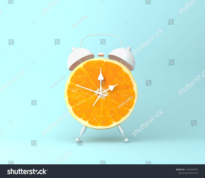 Creative clock background  Creative idea layout fresh orange slice alarm clock on pastel blue