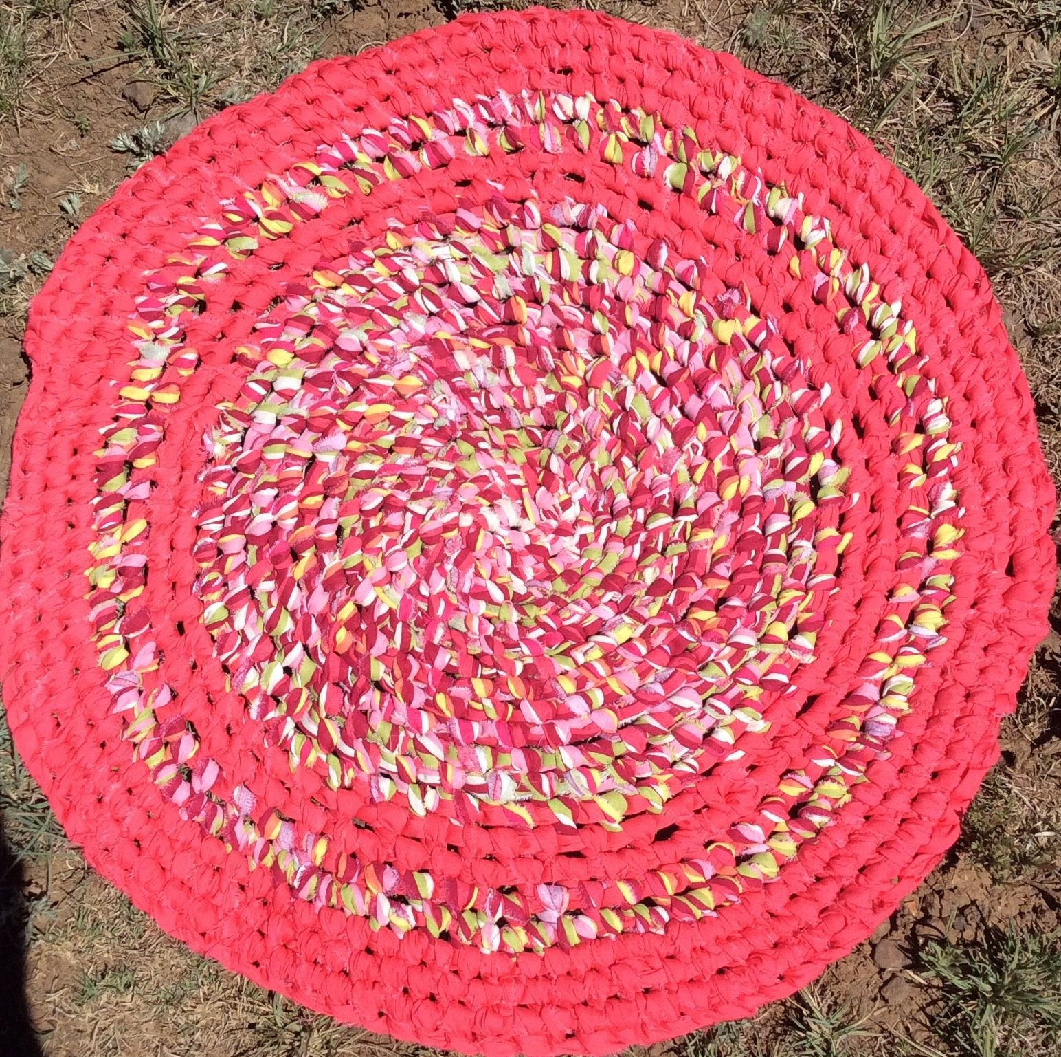 Round coral rug with cranberry, pink green, yellow