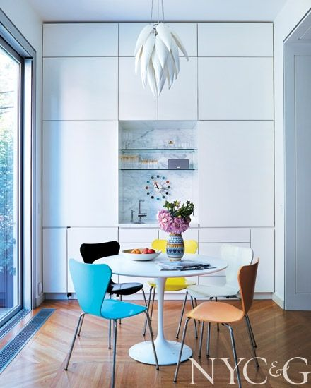 Brooklyn Brownstone designed by Robert Couturier. Colourful Arne Jacobsen Ant chairs amongst a spare white kitchen.