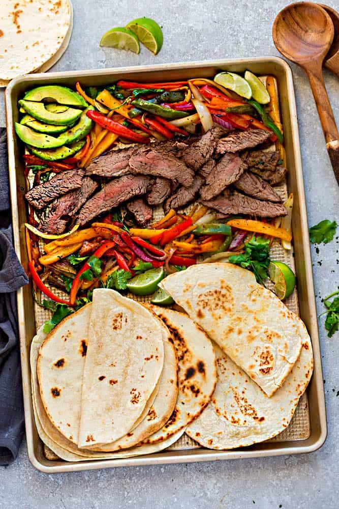 Sheet Pan Steak Fajitas are tender, juicy and full of flavor and perfect for busy weeknights! Best of all, options for low carb and keto with a homemade fajita spice blend and cilantro lime marinade. #steakfajitarecipe