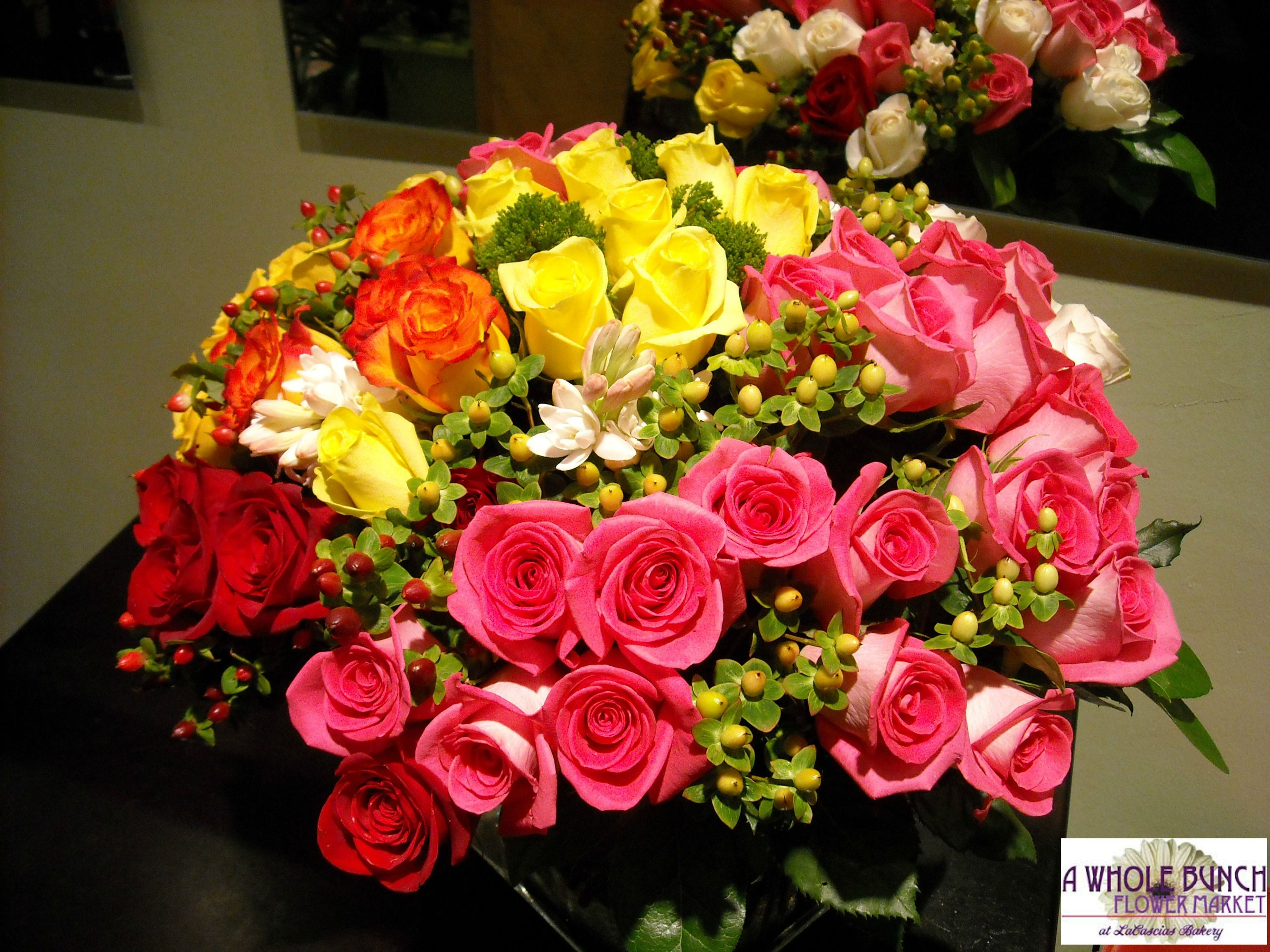 Rainbow mix of roses and other various seasonal flowers make a stunning centerpiece.