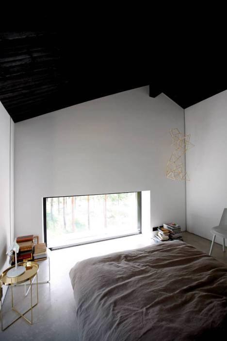 Makuuhuoneen lattian rajassa olevasta ikkunasta voi ihailla mäntymetsää.