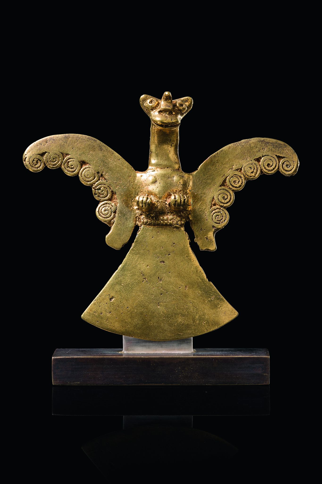 Pectoral bird - Colombia, Sinú gold, weight: 64 gram, cast and hammered, with outstretched wings and fan-like tail, the claws projecting forward, each wing edge with six coils, elongated neck, head with pointed ears and single horn in the middle, eyelet for attachment behind, custom mount; around 1500 B. C.