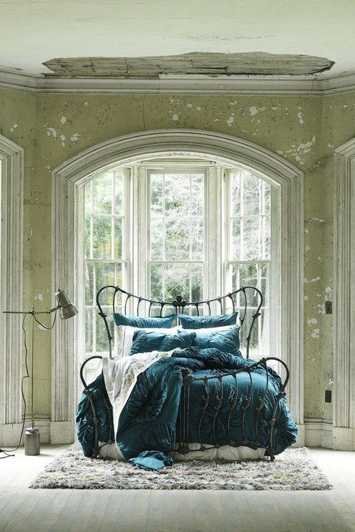 curvy iron bed in front of arched window, distressed walls, teal ...