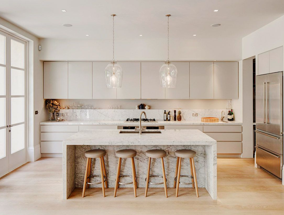 Superb White Kitchen With Wood Stools And Marble Countertop On Island
