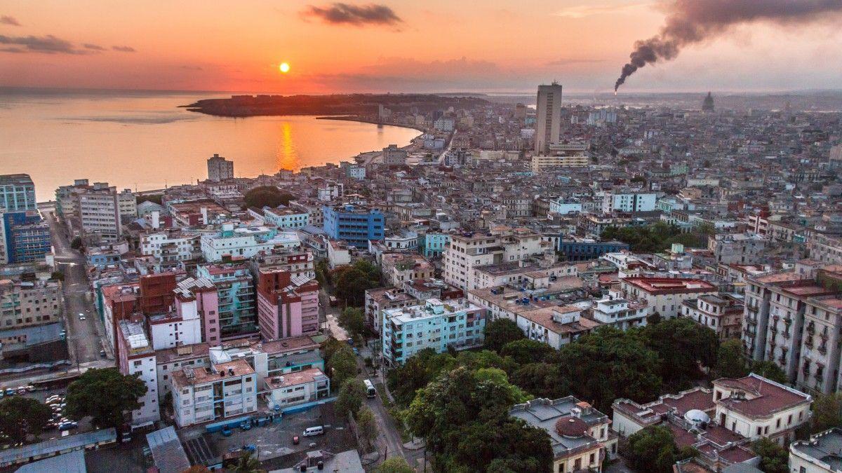 Cuba Malecon sunrise — The sun rises over Havana as smoke rises from an oil  refinery