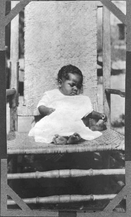 A Young African-American Child In A Caned Rocking Chair