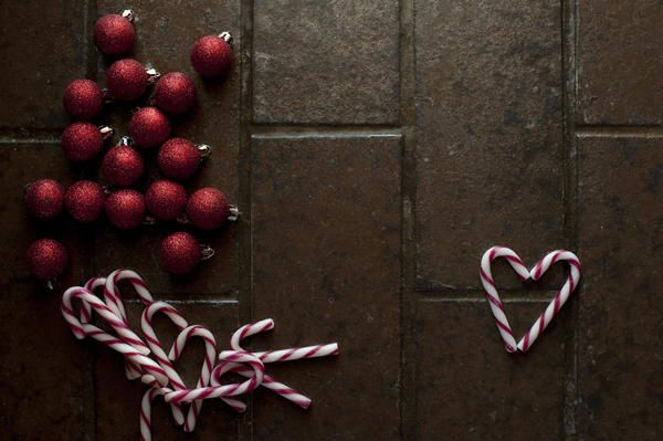 Love this image: Christmas candy background with striped red and white candy canes and baubles on a dark tiled background with two canes formed into a heart and copyspace - By stockarch.com user: raw