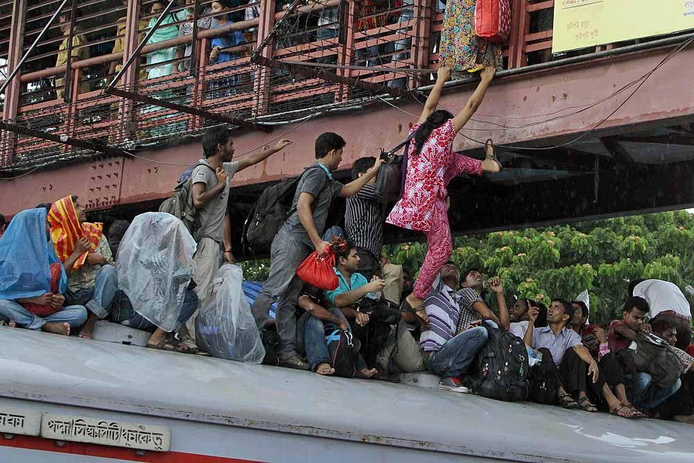 A Bangladeshi woman tries to jump onto an overcrowded train from a bridge to travel home for Eid al-Fitr in Dhaka, Bangladesh. ■ Photo: AM Ahad (AP)