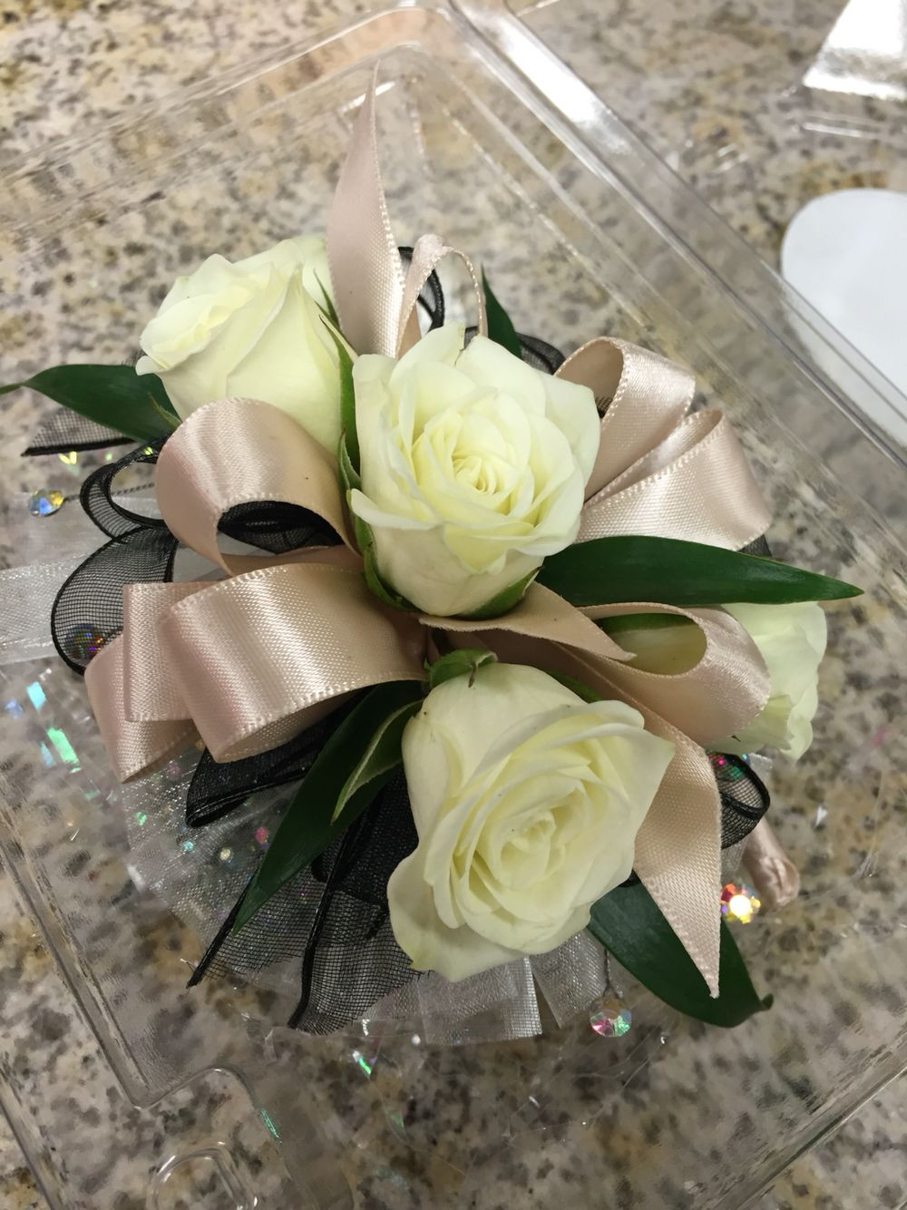 Wristlet corsage with white spray roses, champagne satin ribbon and iridescent…